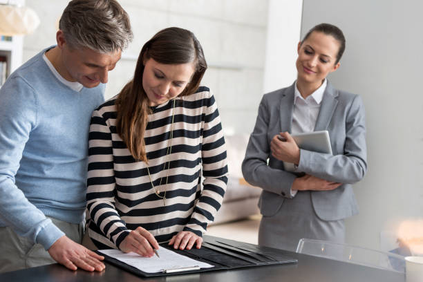 Smiling young saleswoman looking at woman signing contract while standing by man in apartment stock photo