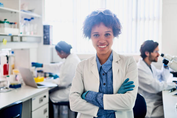 Smiling young scientist standing in a lab with colleagues in the background stock photo