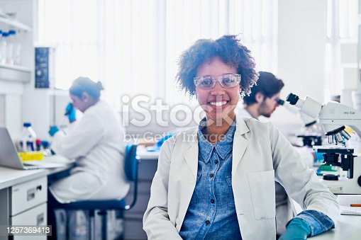 Portrait of a smiling young female scientist sitting a table in a lab with colleagues working in the background