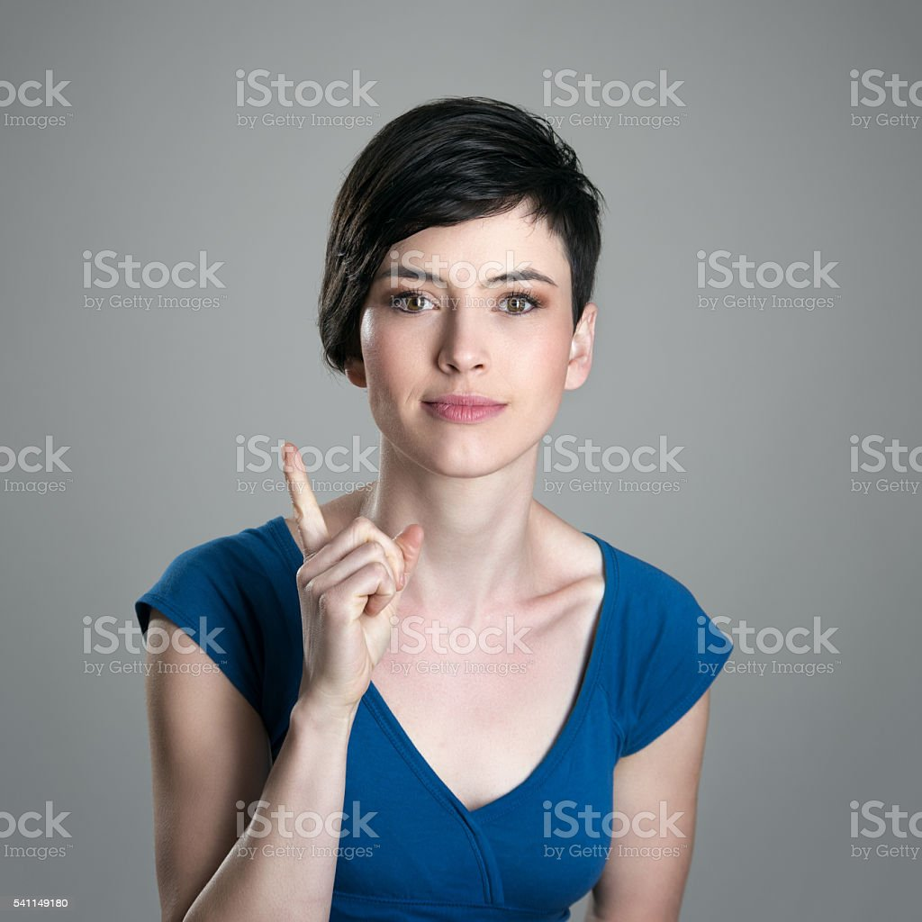 Smiling young short hair woman scolding finger looking at camera stock photo