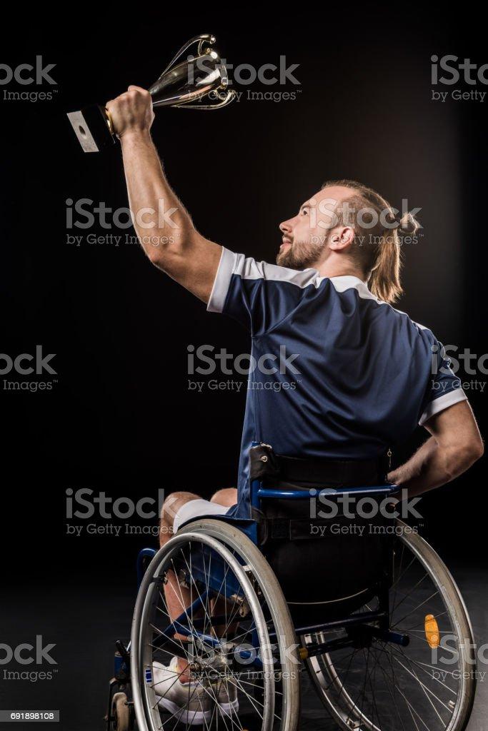黒に分離されたトロフィーを保持している車椅子の若いスポーツマンの笑顔 ストックフォト