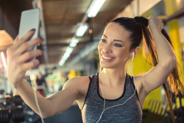 Lächelnde junge Sportlerin, die ein Selfie mit dem Smartphone im Fitnessstudio macht – Foto