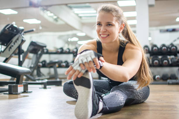 Smiling young sporty girl stretching legs in the gym. stock photo