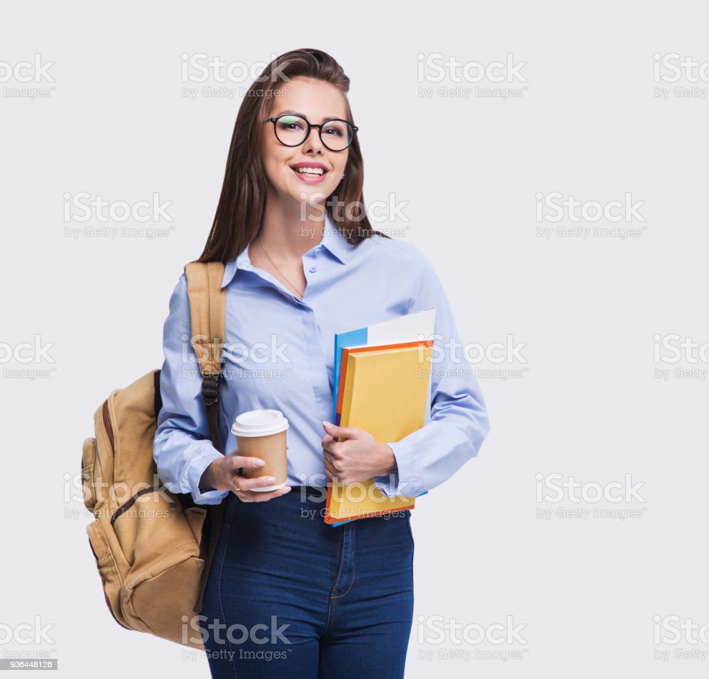 Smiling young student girl holding coffee and books stock photo