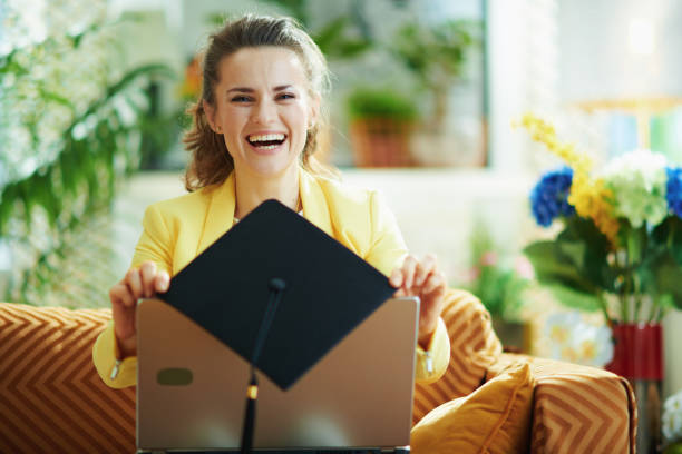 smiling young student showing graduation cap and laptop stock photo
