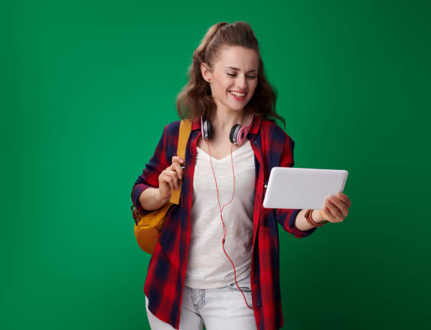 smiling young student woman using tablet pc on green background - ragazza auricolari rossi foto e immagini stock