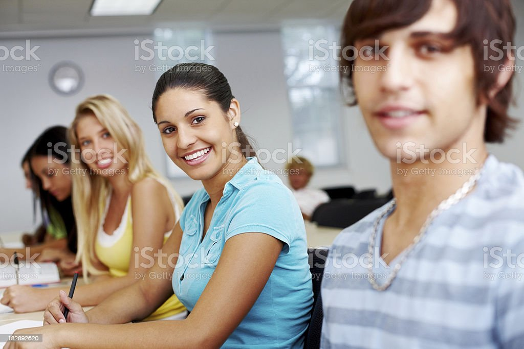 Smiling young students sitting in a row royalty-free stock photo