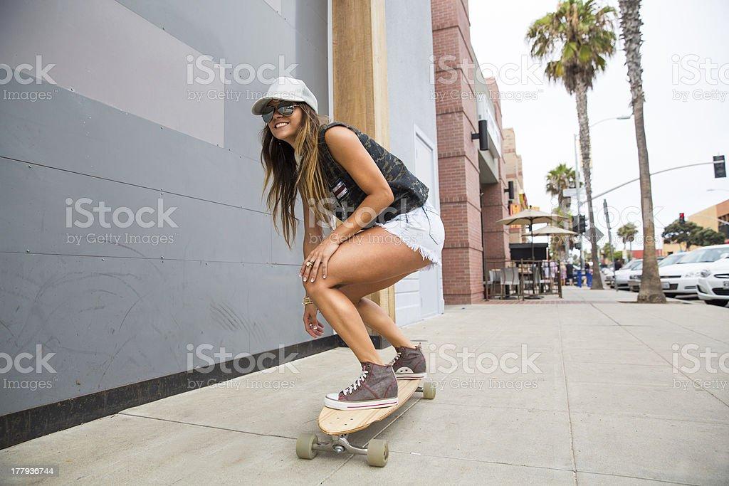 Smiling young teen gilr riding a skateboard. stock photo