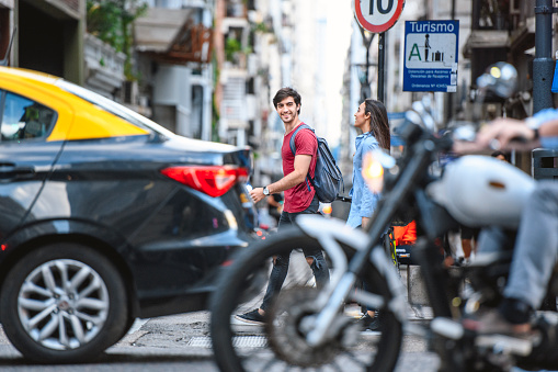 Personal perspective of young male and female vacationers crossing busy street in downtown Buenos Aires.