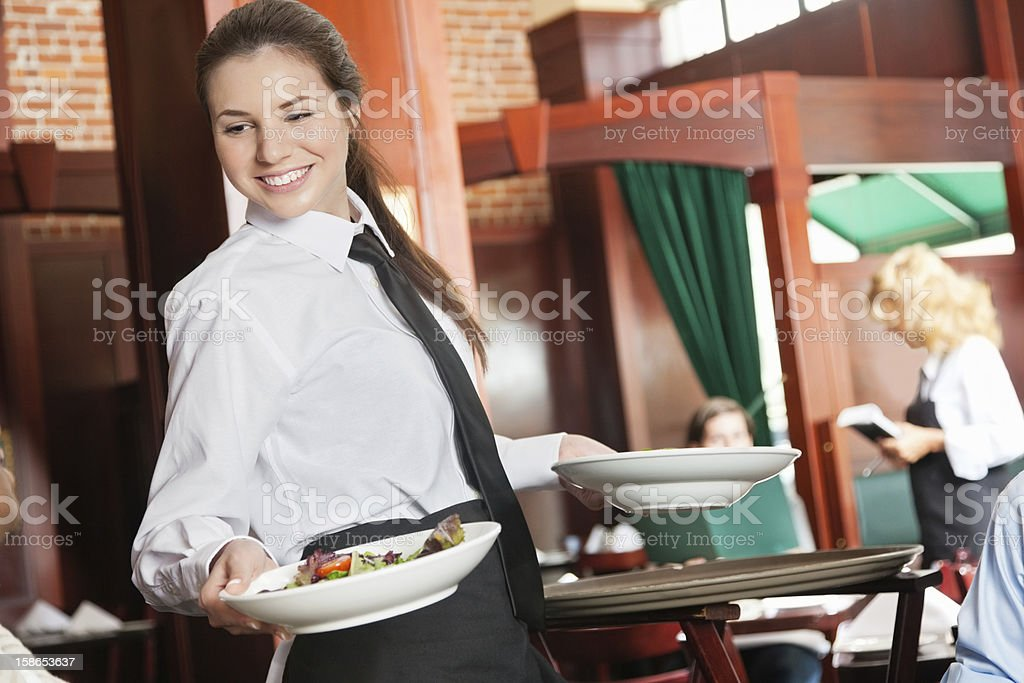 Smiling young waitress serving guests their dinner at nice restaurant stock photo
