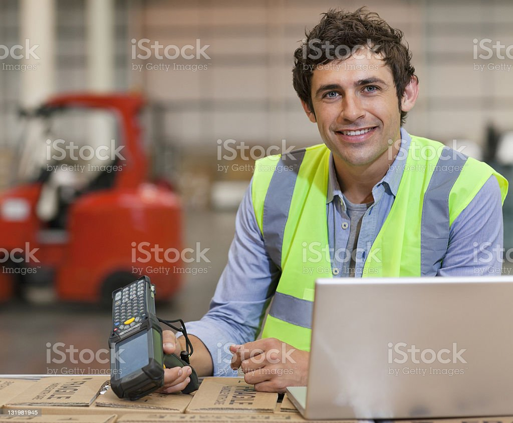 Smiling young warehouse worker with bar code reader and laptop royalty-free stock photo