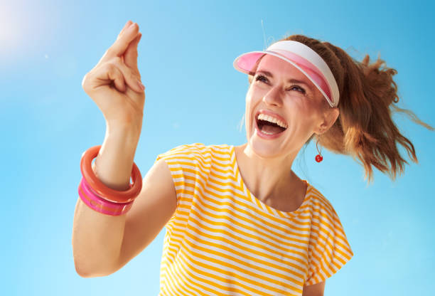 smiling young woman against blue sky fingers snapping smiling young woman in yellow shirt against blue sky fingers snapping snapping stock pictures, royalty-free photos & images