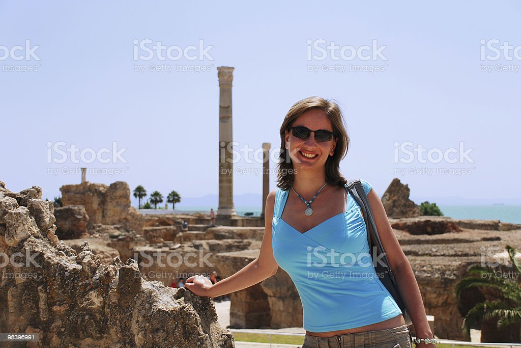 Smiling Young Woman against Ruins of Carthage in Tunisia royalty-free stock photo