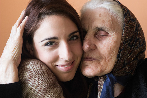 144362548 istock photo Smiling young woman and grandmother embracing 636399810
