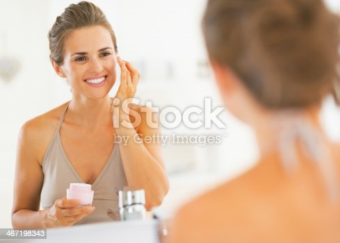 istock A smiling young woman applies face cream in a mirror 467198343