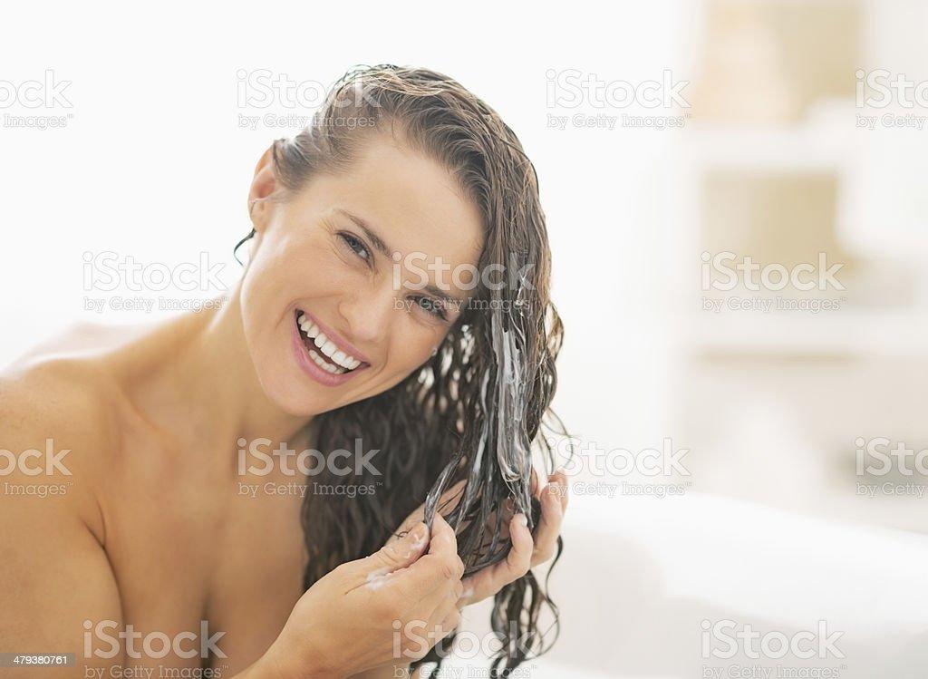 Lächelnde Junge Frau benutzt Haar-conditioner – Foto