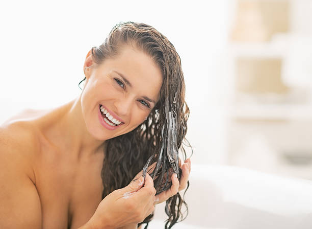 smiling young woman applying hair conditioner - 護髮用品 個照片及圖片檔