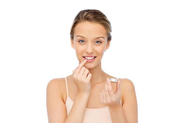 lächelnde junge frau, die anwendung lippenpflege auf ihre lippen - labello stock-fotos und bilder