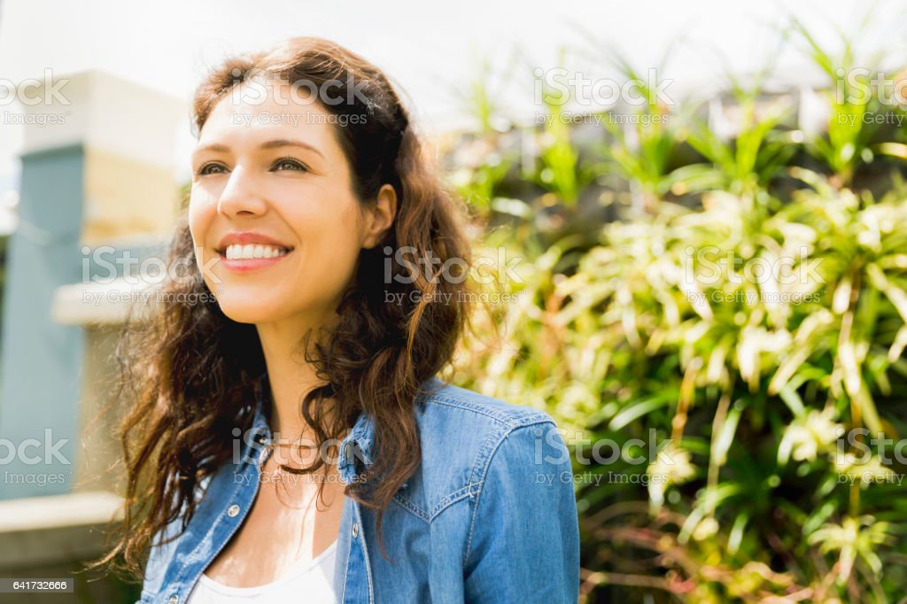 Smiling young woman at community garden stock photo