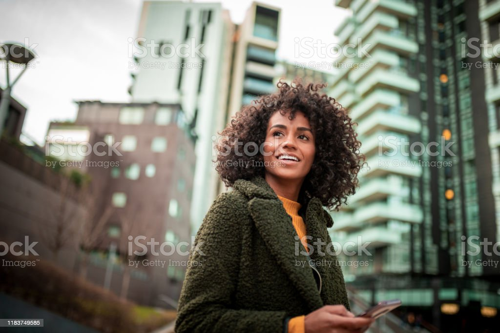 A smiling young woman at the downtown district Smiling young woman waiting for her friend 30-39 Years Stock Photo