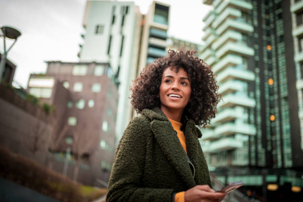 A smiling young woman at the downtown district Smiling young woman waiting for her friend looking away stock pictures, royalty-free photos & images
