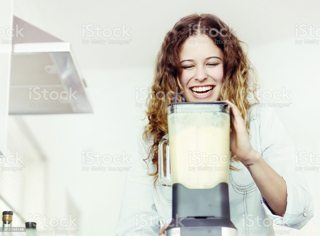 Smiling young woman busy in kitchen with blender, making smoothie stock photo
