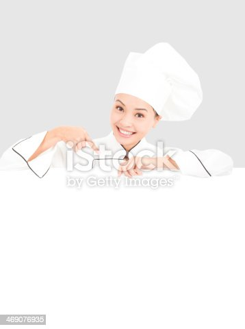 istock smiling  young woman chef pointing  with blank board 469076935