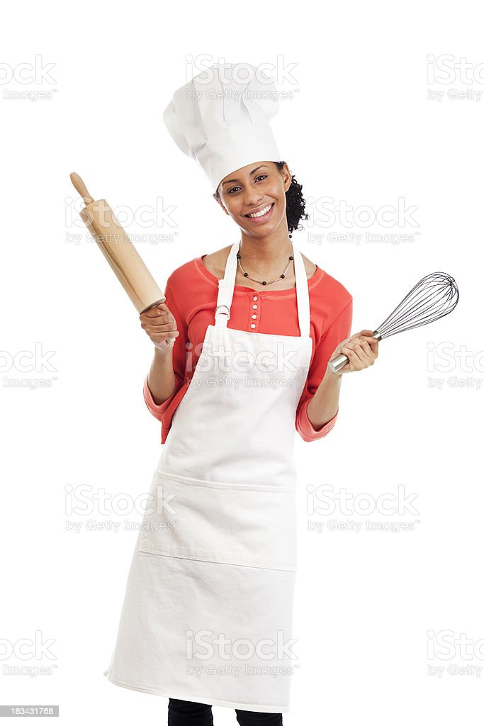 Smiling Young Woman Chef with Apron, Hat, and Kitchen Utensils stock photo
