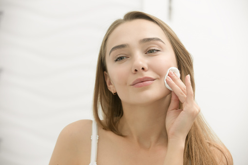 istock Smiling young woman cleaning her skin with a cotton pad, 625205914