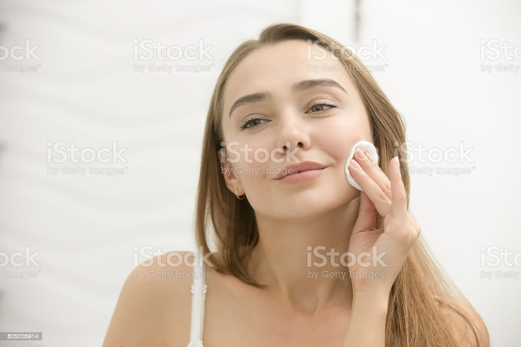 Smiling young woman cleaning her skin with a cotton pad, stock photo