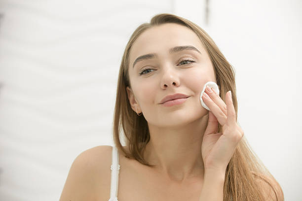 smiling young woman cleaning her skin with a cotton pad, - beautiful curvy girls stock photos and pictures