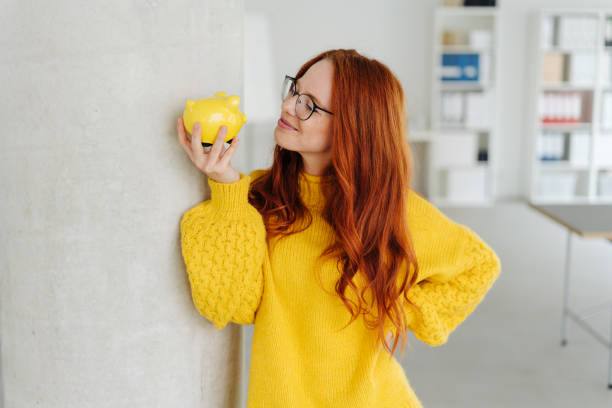 Smiling young woman contemplating a piggy bank stock photo