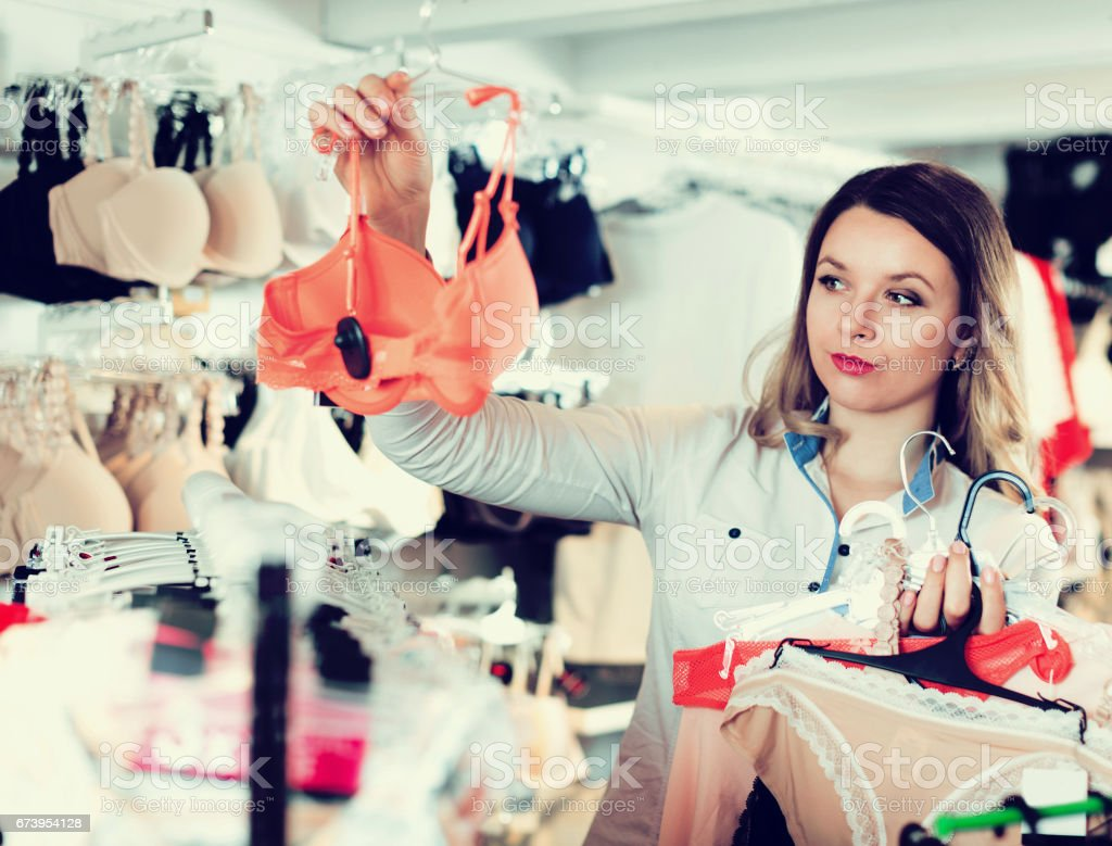 Smiling young woman customer choosing lingerie royalty-free stock photo