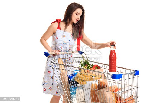 Smiling young woman doing grocery shopping at the supermarket, she is putting a tomato juice bottle in the cart isolated on white background. Brunette in a summer dress makes purchases