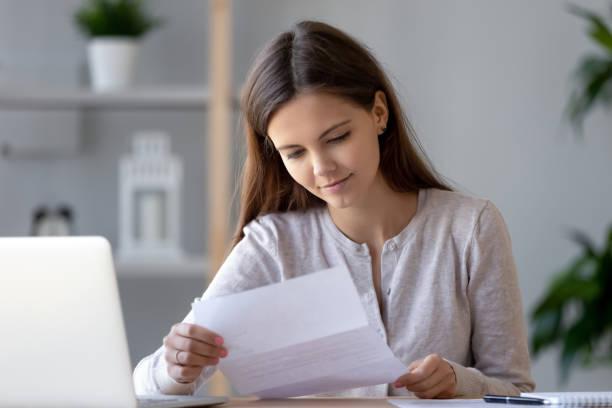 улыбаясь молодая женщина делает документы чтение письма или законопроекта - письмо документ стоковые фото и изображения
