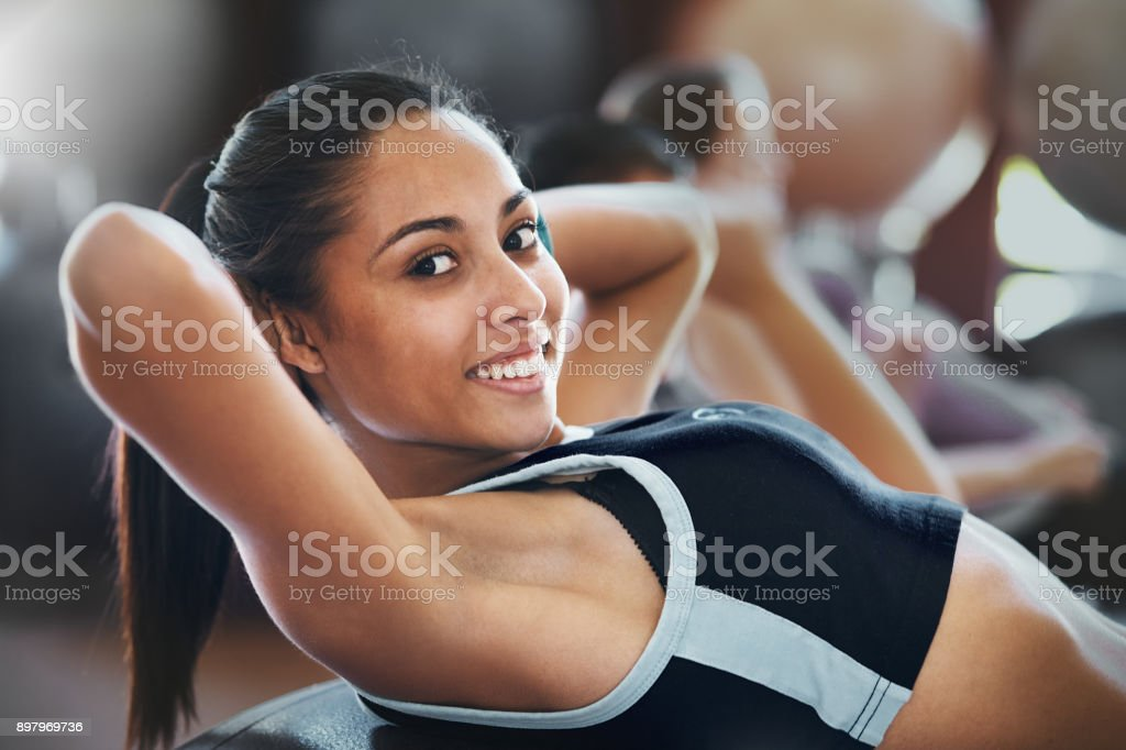 Smiling young woman doing sit-ups at health club stock photo