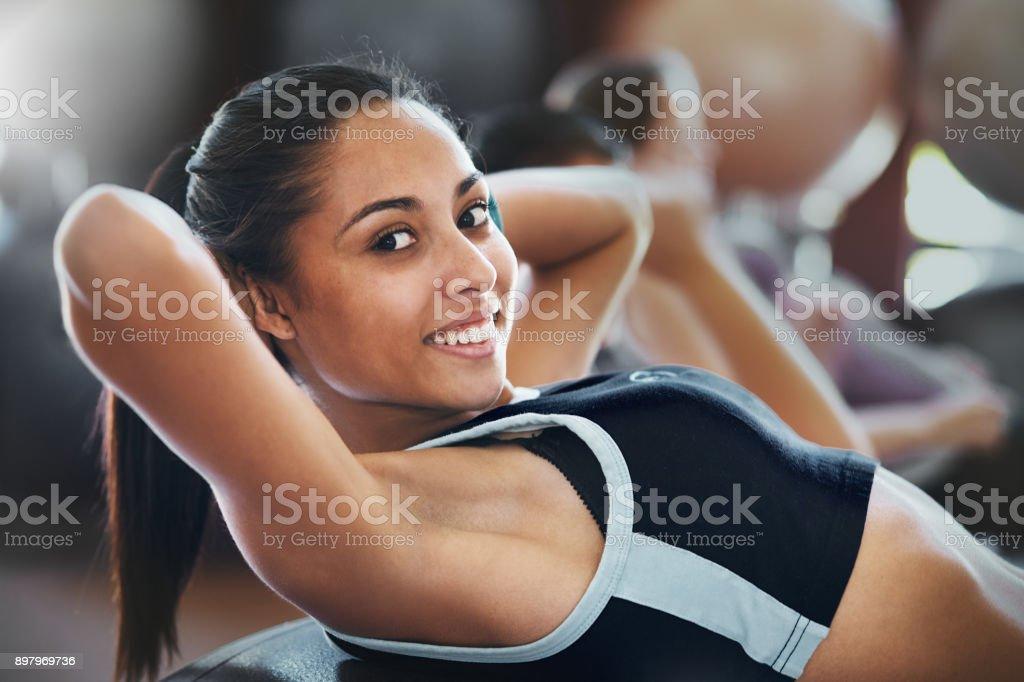 Souriante jeune femme faisant des sit-ups au club de santé - Photo