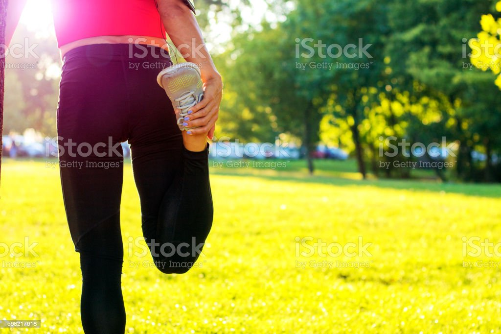 Smiling young woman doing stretching exercise at sunset foto royalty-free