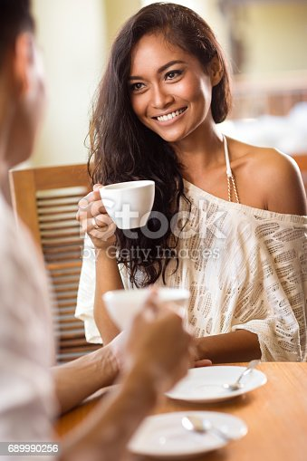1065243116 istock photo Smiling young woman drinking coffee looking her boyfriend 689990256