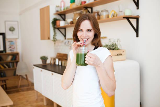 leende ung kvinna dricker grön smoothie juice i köket. hälsosam livsstil. - spirulinabakterie bildbanksfoton och bilder