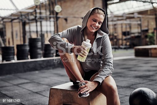 Sporty young blonde woman wearing a hoodie smiling and drinking water while sitting on a box at the gym after a workout