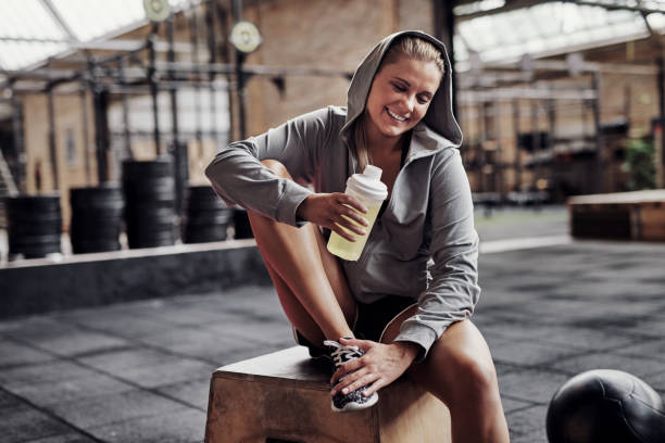 Smiling young woman drinking water while sitting in a gym picture id911681242?b=1&k=6&m=911681242&s=612x612&w=0&h=ruxwopnoeqwtykpmoygyeval nv4so2dxlqrgc15t6y=