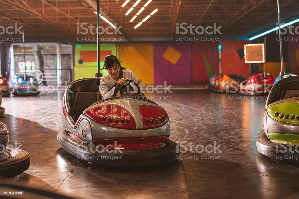 Smiling young woman driving a bumper car – Foto
