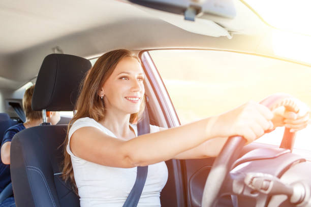 Smiling young woman driving a car at summer day Smiling young woman driving a car at summer day with her son on the back seat sergionicr stock pictures, royalty-free photos & images