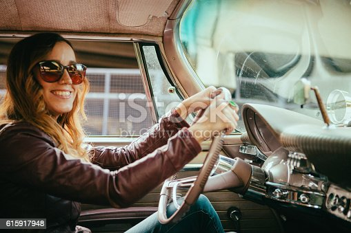Driver seat portrait of a cute young woman smiling while driving a vintage American car. She has the window down and arms out the window as she peacefully cruises in this classic car. Road trip adventure stock!!!