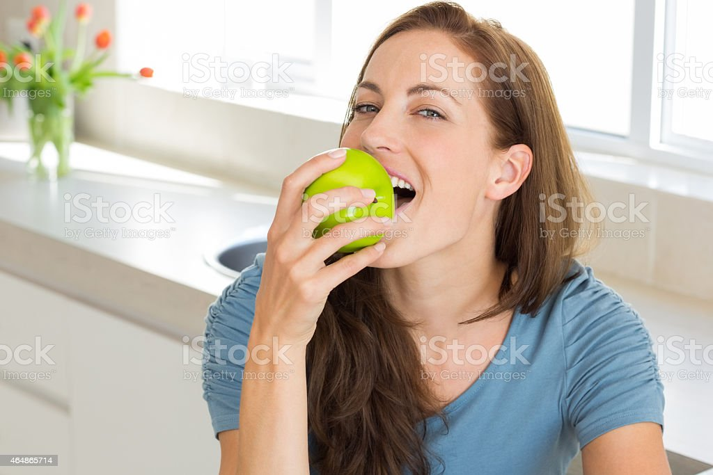 Smiling young woman eating apple in kitchen stock photo