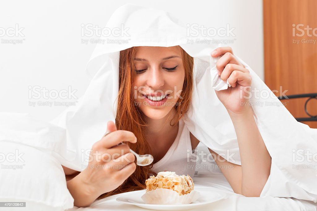 Smiling young woman eating sweet cake stock photo