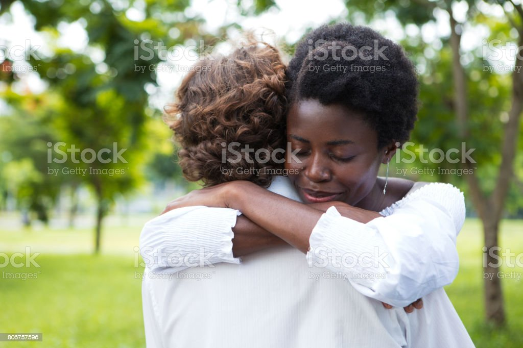 Smiling young woman embracing her boyfriend stock photo