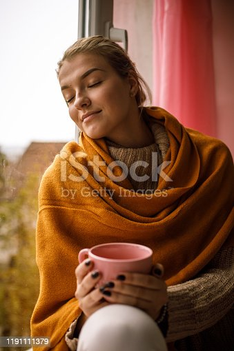 909062786 istock photo Smiling young woman enjoying a cup of tea and relaxing 1191111379