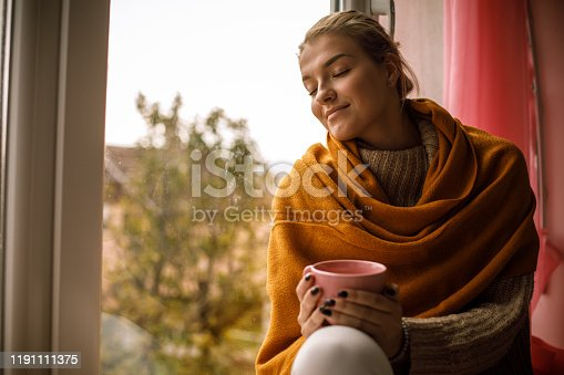 909062786 istock photo Smiling young woman enjoying a warm cup of tea on a cold autumn day 1191111375